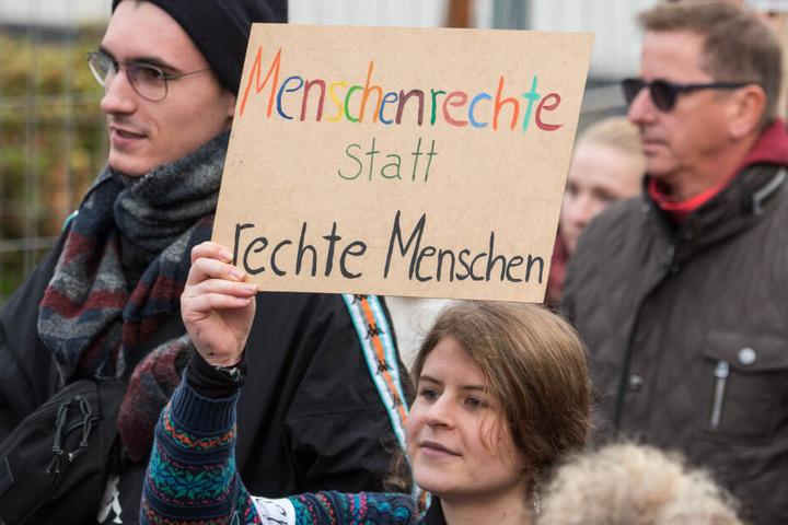 """Teilnehmer einer Demonstration gegen Neonazis und rechte Gewaltziehen durch die Innenstadt und halten ein Schild mit der Aufschrift """"Menschenrechte statt rechte Menschen"""". (Symbolbild)"""