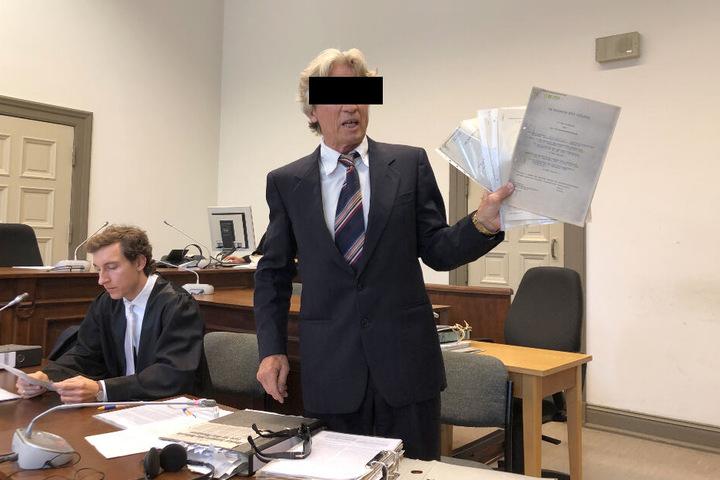 Der Anklagte hält einen Stapel von Papieren in seinen Händen.