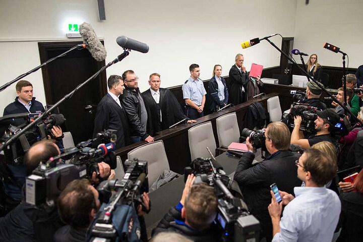 Der ohnehin kleine Gerichtssaal ist beim Eintreffen der Angeklagten komplett gefüllt! Während Wilfried W. sich der Öffentlichkeit präsentiert, versteckt sich Angelika W. hinter einer roten Akte. Das Medieninteresse ist groß.