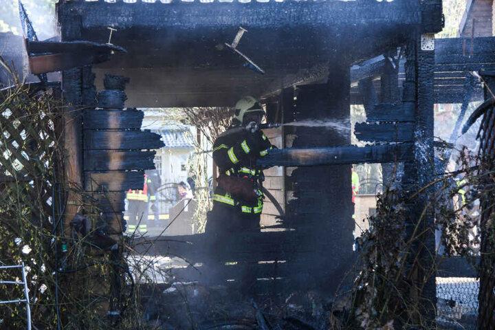Ein Feuerwehrmann steht im abgebrannten Carport.