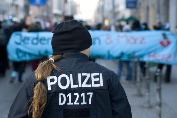 Eine Polizistin beobachtet am 08.03.2012 in Berlin im Bezirk Mitte Teilnehmerinnen einer Demonstration linker Frauengruppen zum Weltfrauentag.