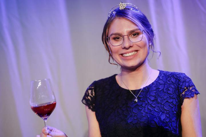 Die baden-württembergische neue Weinkönigin Tamara Elbl hält ein Glas Wein in der Hand.