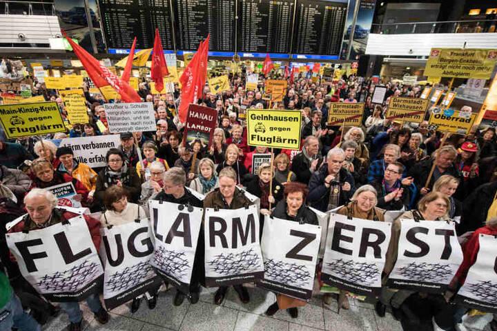 Immer wieder wird gegen Fluglärm demonstriert. Hier stehen Kundgebungsteilnehmer 30.01.2017 mit einem Fluglärm-Plakat im Terminal A des Frankfurter Flughafens.