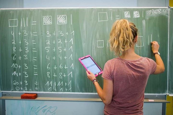 BU-A-Lehrerin-an-Tafel: Nach wie vor gibt es nicht genügend Lehrer. Selbst wenn Stellen durch Fachkräfte besetzt sind - viele arbeiten in Teilzeit.