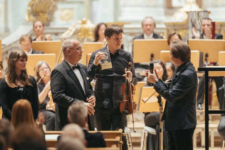 Joshua Bell (51) am Montagabend in der Frauenkirche. Die Preistrophäe ist wie jedes Jahr von zwei Uhrmacherlehrlingen der Firma Glashütte Original gebaut worden.