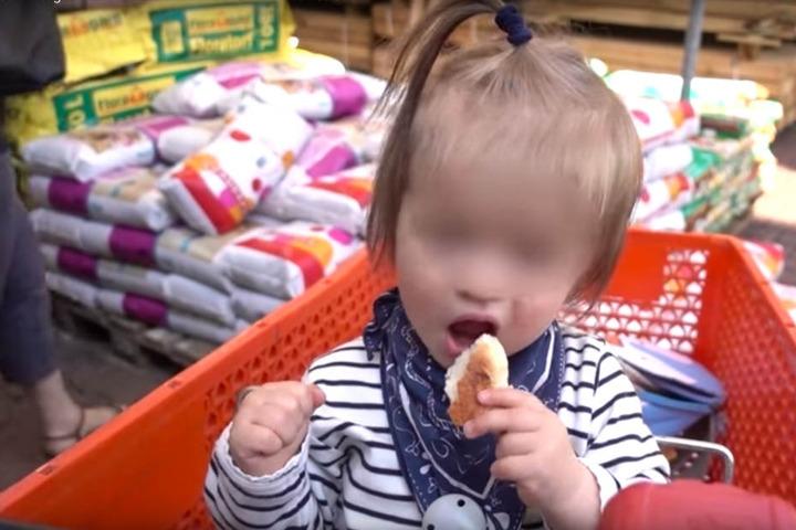 Während Mama und Papa einkaufen, knabbert Ella an ihrem Brötchen.