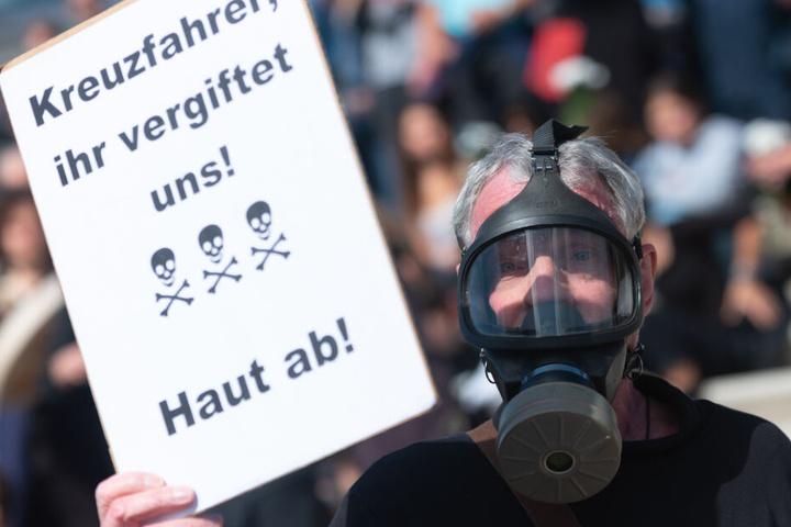 """Ein Mann posiert mit einer Gasmaske und einem Protestplakat während einer Protestaktion der Gruppe """"Extinction Rebellion"""" in Hamburg."""