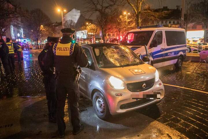 Polizisten begutachten den zerstörten Unfallwagen.
