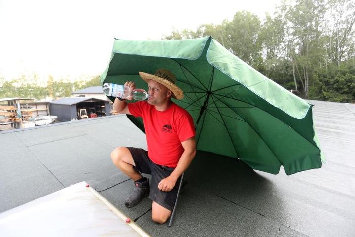 Dachdeckermeister Gordon Tillmann (46) flüchtet bei tropischen Temperaturen unter seinen Sonnenschirm.