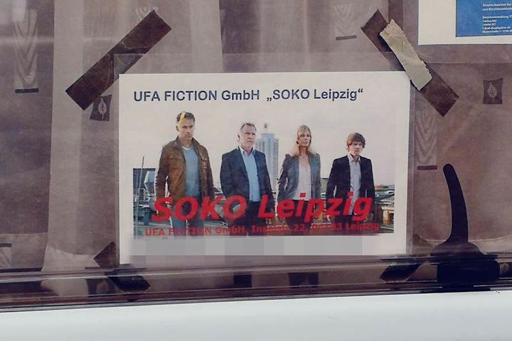 """Im Fenster eines Wohnwagens hängt ein Schild, das erahnen lässt, dass am Floßplatz für """"SOKO Leipzig"""" gedreht wurde."""
