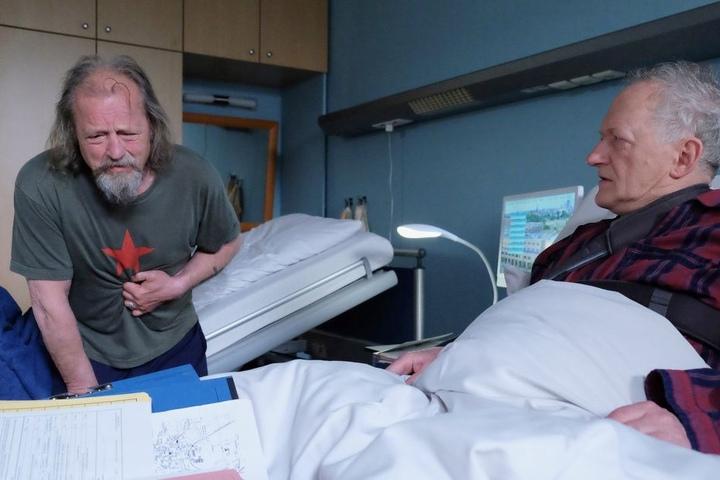 In der Sachsenklinik bezieht er ausgerechnet mit seinem ungeliebten Bruder Thomas (r.) ein Zimmer. Dort facht der Streit wieder auf. Doch plötzlich bricht Wolfgang zusammen. Wie reagiert sein Bruder?