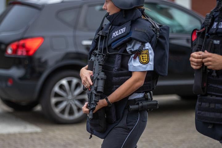 Zu sehen ist eine Polizistin mit Maschinengewehr am Einsatzort.