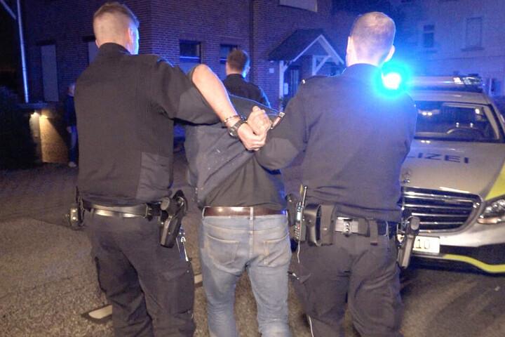 Polizisten haben dem Ersthelfer Handschellen angelegt und führen ihn ab.