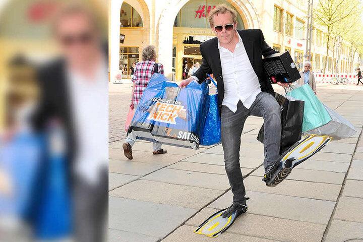 Schauspieler Felx Voigt (47) stapft mit Flossen und Einkaufstzaschen durch die City.