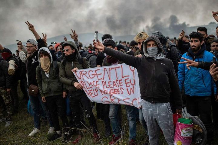 """Protestierende Migranten halten ein Banner mit der Aufschrift """"Schnell, Bitte, Bitte EU, helft den Migranten in Griechenland""""."""