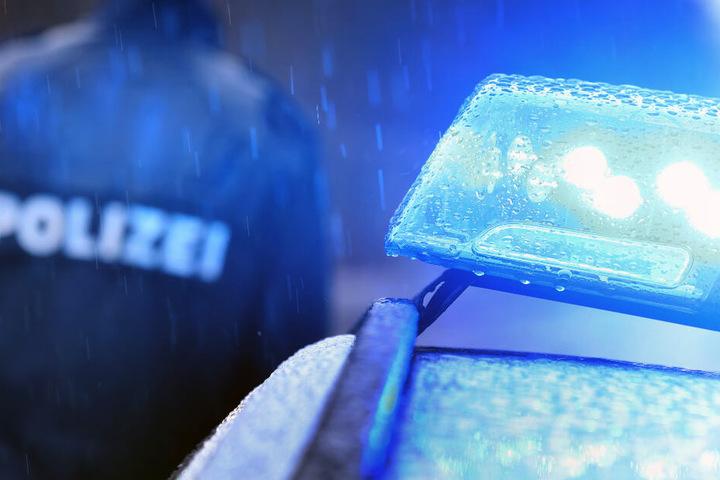 Ein Polizist steht im Regen neben einem Einsatzfahrzeug mit leuchtendem Blaulicht.