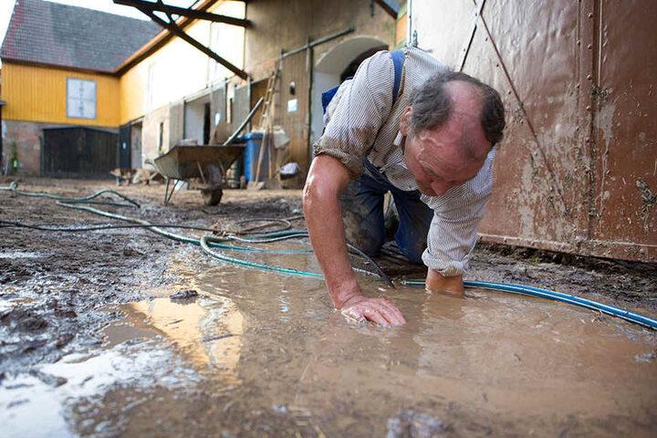 Ein Anwohner versucht nach dem starken Unwetter in Bad Bibra mit einem Gartenschlauch einen Regenabfluss zu entstopfen. Hagelkörner so groß wie Hühnereier zerschossen die Regenrinnen und die Schlammmassen durchbrachen das Tor.