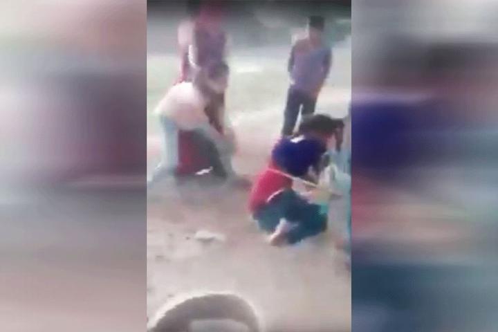 Eine Frau schlägt auf das Opfer ein.
