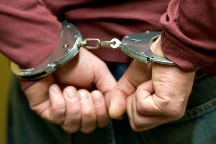Ein Mann wird in Handschellen abgeführt. (Symbolbild)