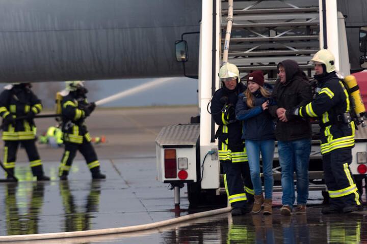Die Feuerwehrmänner bringen zwei Menschen aus dem Flugzeug.