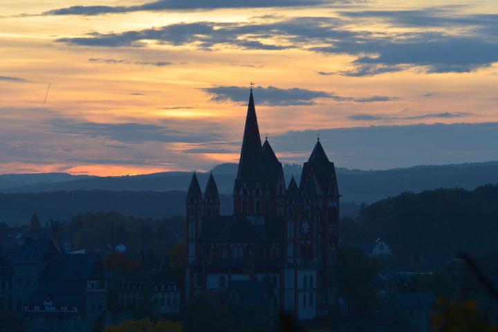Die Sonne geht hinter dem Limburger Dom unter.