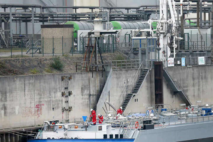 Ein Schiff an einer Rhein-Kaimauer liegt tief im Hafenbecken.