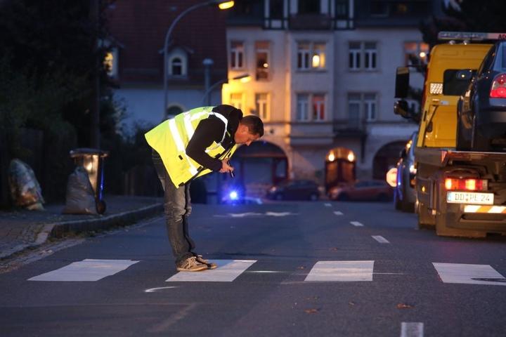 Ein Ermittler sucht mit einer Taschenlampe nach Spuren des schrecklichen Unfalls.