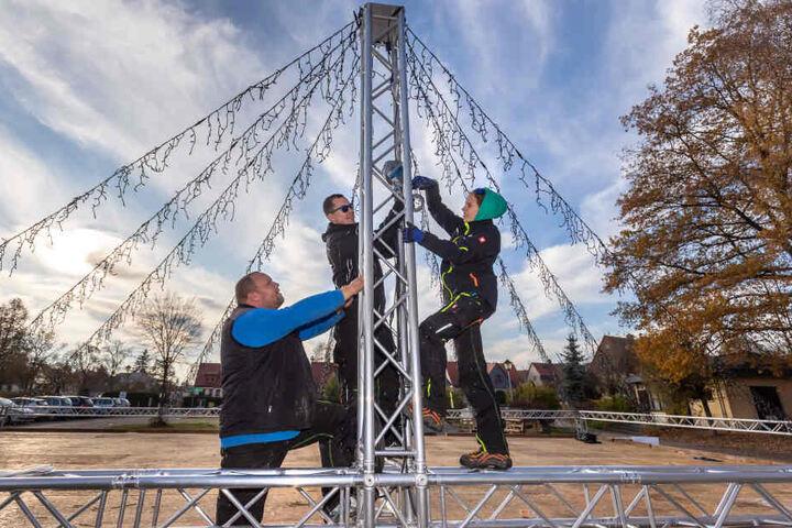 Benjamin Weigel (28, v.l.), Moritz Rotter (21) und Daniela Hähner (22) montieren die Lichterketten für das Dach der Eisbahn in Oederan.