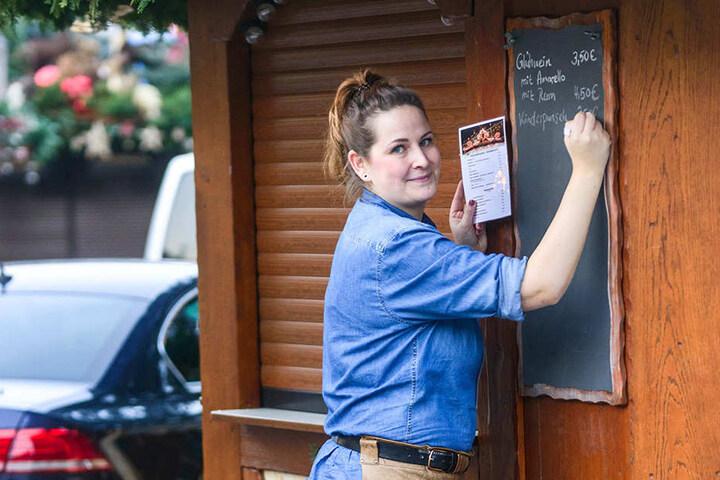 """Anke Lehmann (29) schreibt mit Kreide Glühwein- und Punsch-Preise auf eine Tafel am """"Punsch Türmchen""""."""