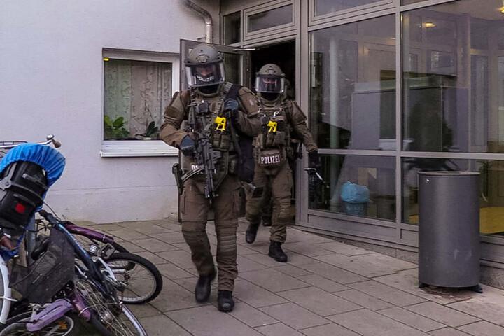 Bewaffnete Einsatzkräfte verlassen nach der Stürmung der Wohnung das Haus.