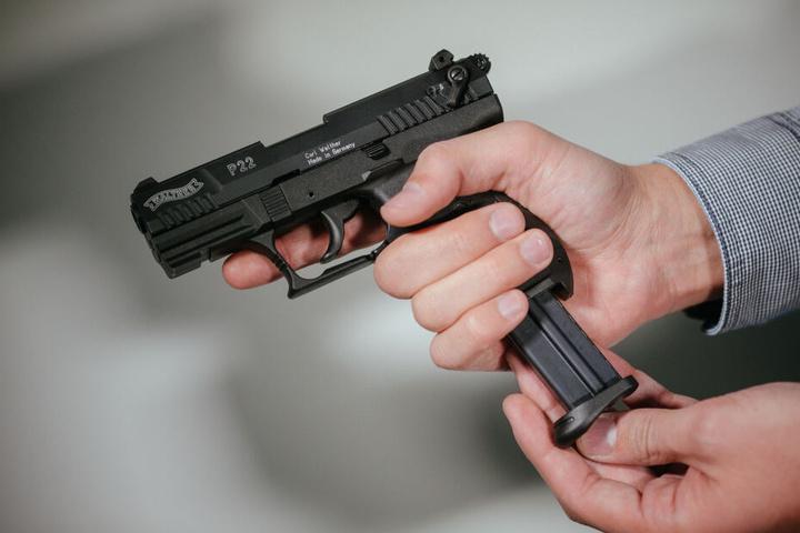 """Hände laden eine Schreckschuss-Pistole """"Walther P22"""" mit einem Magazin."""
