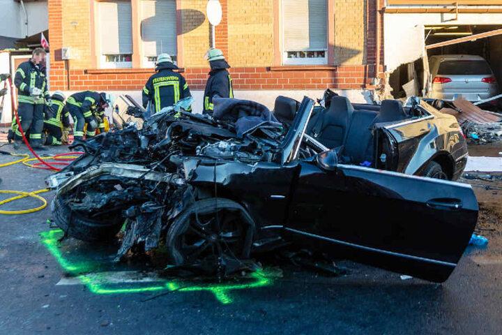 Im Hintergrund des Fotos ist die beschädigte Hauswand samt Garage zu sehen.