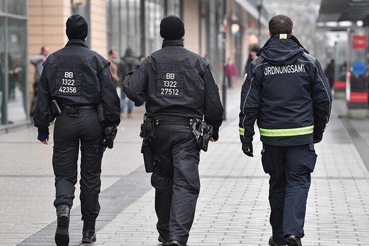 Ein Mitarbeiter des Ordnungsamtes und zwei Beamte der Bereitschaftspolizei auf Streife vor dem Einkaufszentrum Blechen Carré in Cottbus.
