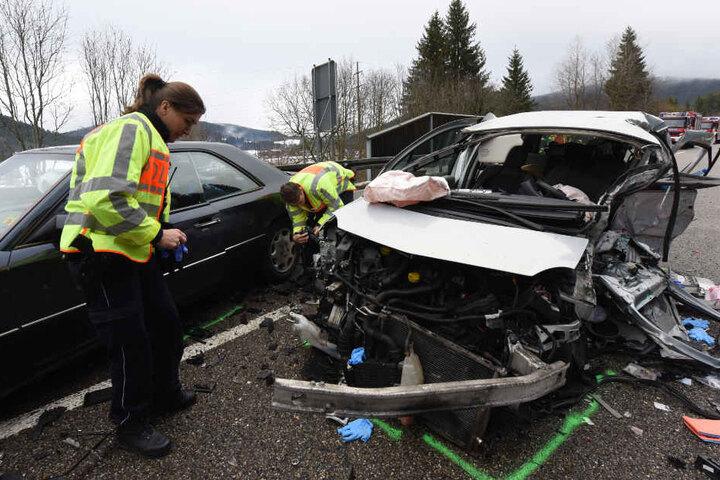Polizisten untersuchen das Wrack des Renaults. Die beiden Insassen kamen ums Leben.