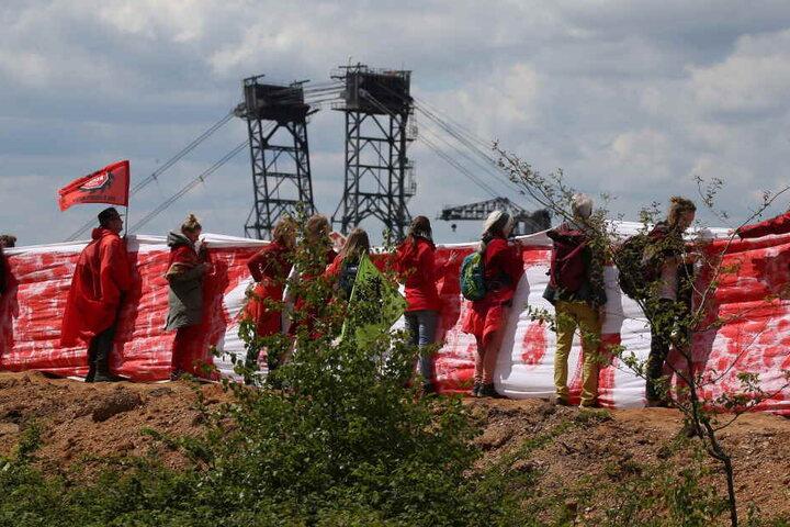 Die Aktivisten zogen dabei mit Transparenten eine Rote Linie, die die Braunkohlebagger nicht überschreiten sollen.