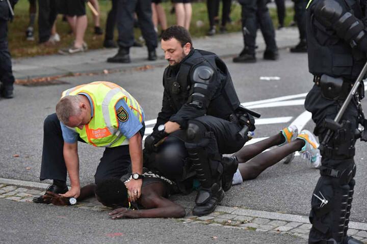 Polizisten nehmen einen lybischen Asylbewerber fest, der aus dem linken Lager zu dem Gegner durchbrechen wollte.
