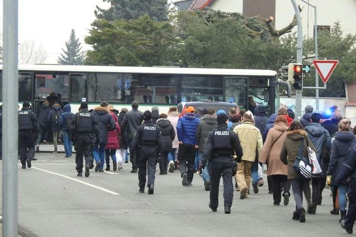 Die Schüler werden unter Begleitung der Polizei zu den Bussen gebracht, die sie in eine Grundschule fahren.