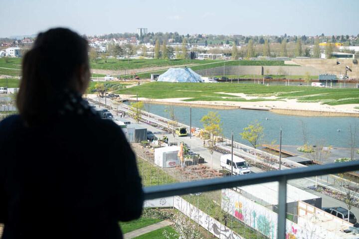 Eine Frau blickt von einem Wohngebäude der Stadtausstellung auf das Gelände der Bundesgartenschau.
