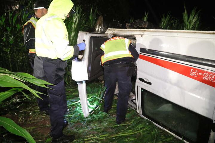 Die Polizisten untersuchen den Unfallwagen.