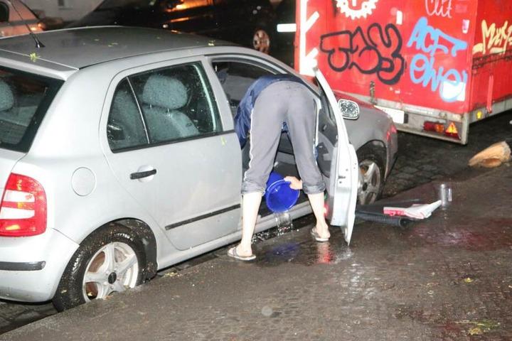 Auto-Besitzer versuchen ihre Wagen mit Eimern von den großen Wassermengen zu befreien.