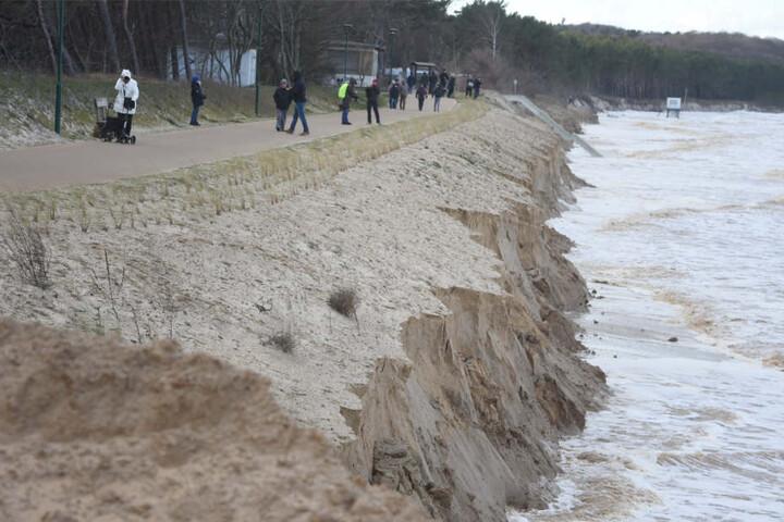 Menschen laufen auf einem Weg in Zempin am Meer entlang. Hier hat die Sturmflut ganze Küstenabschnitte abgetragen.
