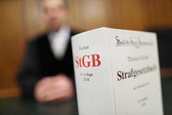 Ein Strafgesetzbuch (StGB) steht im auf der Richterbank. (Symbolbild)