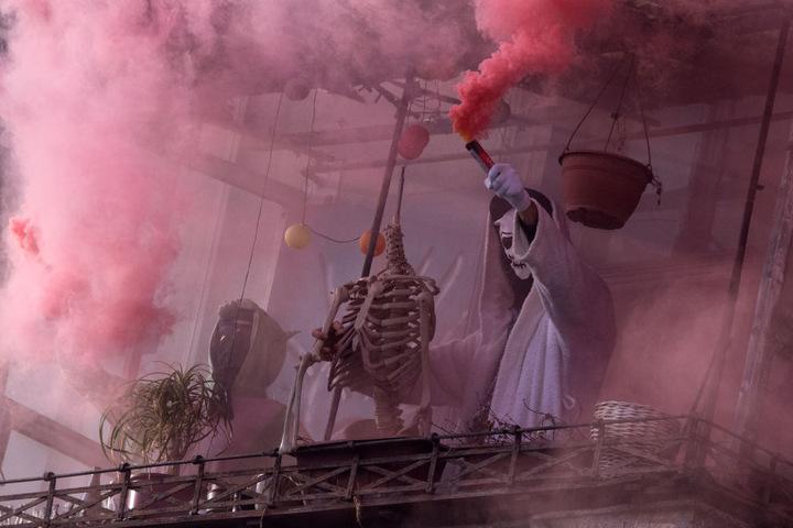 Verkleidete Demonstranten protestieren auf dem Balkon eines Hauses mit Rauchfackeln.