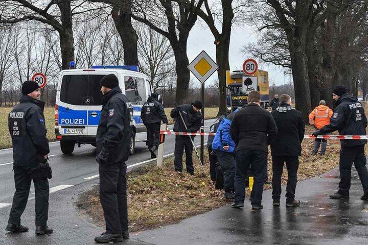 Polizisten stehen an der Stelle, wo zwei ihrer Kollegen starben und suchen nach Spuren.