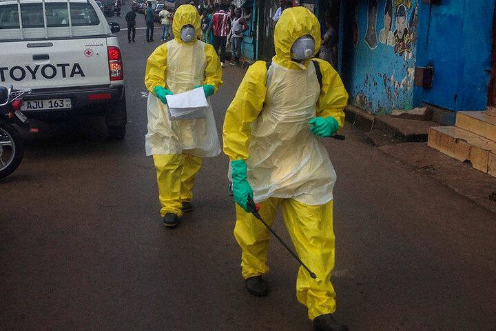 In Schutzanzügen gehen Männer durch eine Straße in Sierra Leone nach einer Ebola-Epidemie.