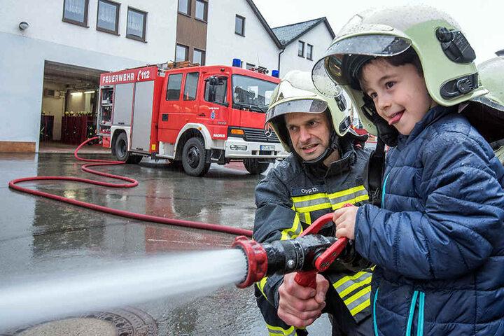 Das macht Spaß! Bilal (5) probierte mit Feuerwehrmann Daniel Opp (38) den Wasserschlauch aus.