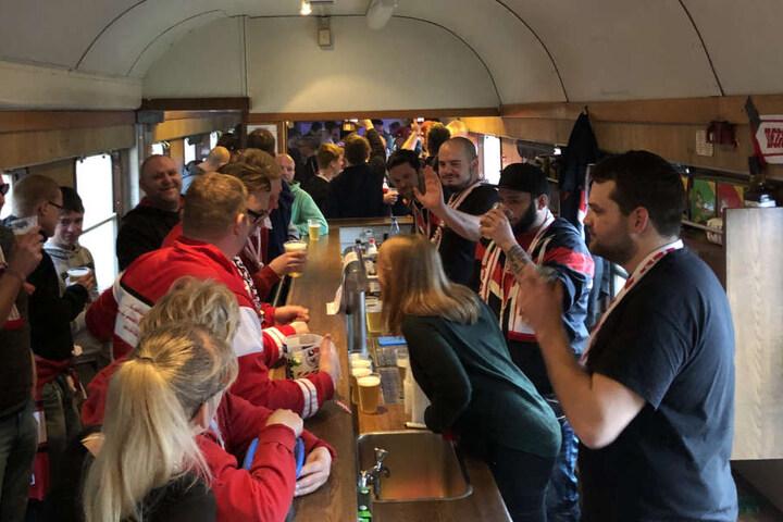 Norman Pilling (r.), Fan-Beauftragter der Eispiraten und Hauptorganisator der Zugfahrt, half im Patry-Waggon beim Ausschenken der Getränke.