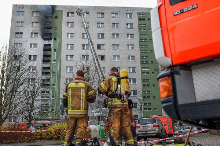 Zwei Feuerwehrmänner stehen nach ihrem Einsatz vor dem brennenden Hochhaus.
