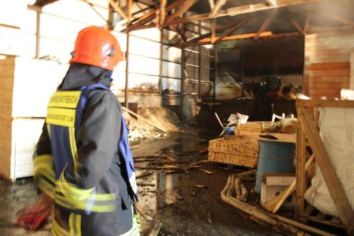 Ein Feuerwehrmann macht sich ein Bild von der gelöschten Brandstelle.