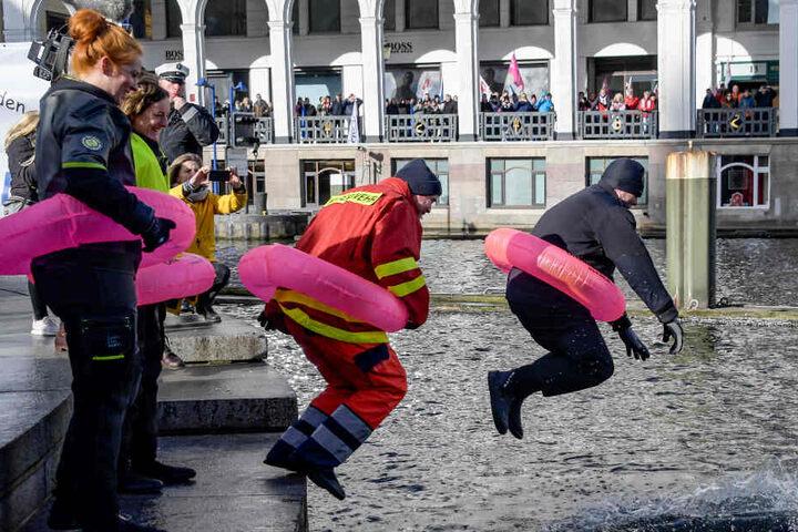 Mitarbeiter im öffentlichen Dienst springen mit Rettungsringen in die Binnenalster.